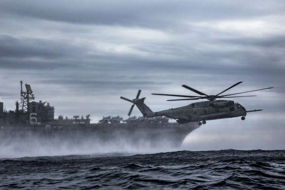 A Sikorsky CH-53E Super Stallion flies next to the USS Bonhomme Richard during an exercise in the Pacific Ocean in 2017. Photo: Marine Corps. Photo By Cpl. Jona R. Meme
