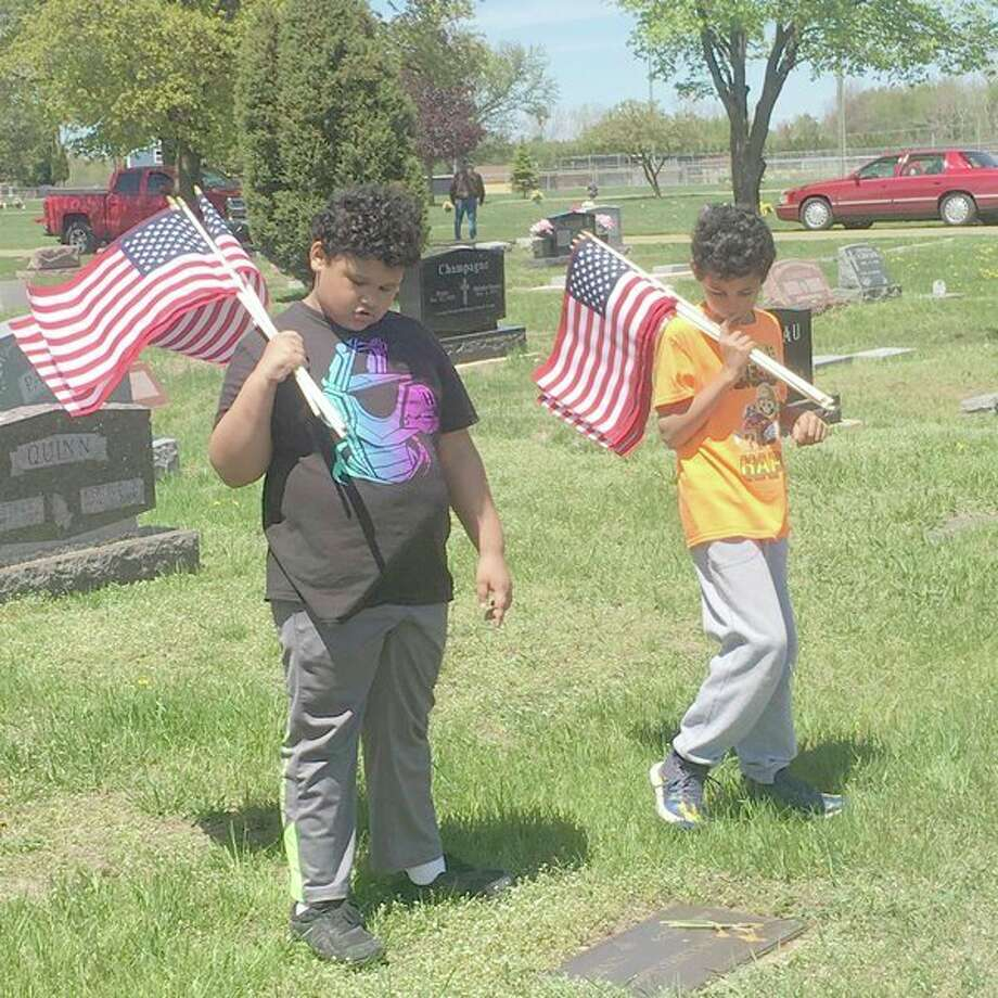 Some Bad Axe Middle School students, veterans and other community members gathered this week to place flags on veteran graves in Bad Axe. (Submitted Photo)