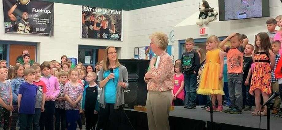 Laker Elementary Counselor Becky Krohn, along with some help from students Austin Zarnke and Joshua Hartman, present Dickens with a special book filled with pages of memories and good wishes written by students and staff members. (Submitted Photo)
