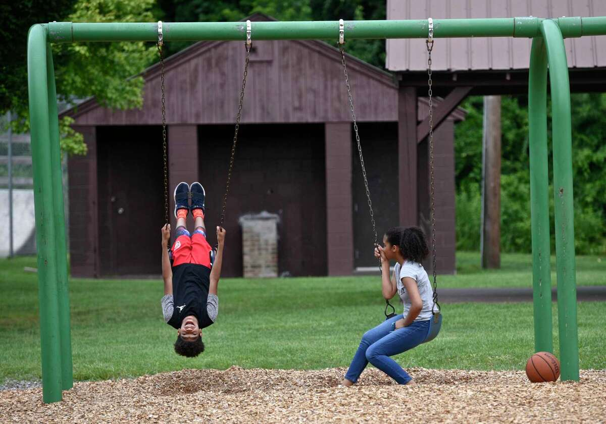 File photo of children play on the swings in Young's Field Park, New Milford, Conn.