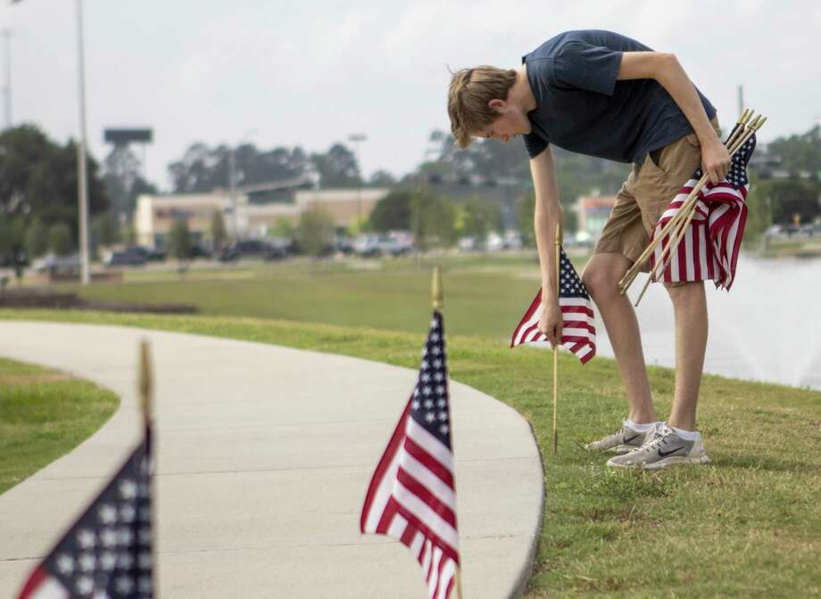 Boy scout Johna Wendt plants flags Thursday, May 23, 2019 at the intersection of I45 and TX 105 in Conroe. Volunteers helped plant around 1,000 flags. Photo: Cody Bahn, Houston Chronicle / Staff Photographer / © 2018 Houston Chronicle