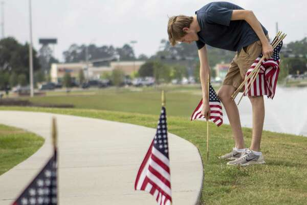 Boy scout Johna Wendt plants flags Thursday, May 23, 2019 at the intersection of I45 and TX 105 in Conroe. Volunteers helped plant around 1,000 flags.