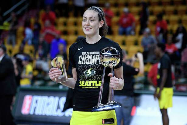 Seattle Storm forward Breanna Stewart poses with the finals mvp trophy and the WNBA championship trophy after Game 3 of the WNBA basketball finals against the Washington Mystics, Wednesday, Sept. 12, 2018, in Fairfax, Va. The Storm won 98-82 and the title. (AP Photo/Nick Wass)