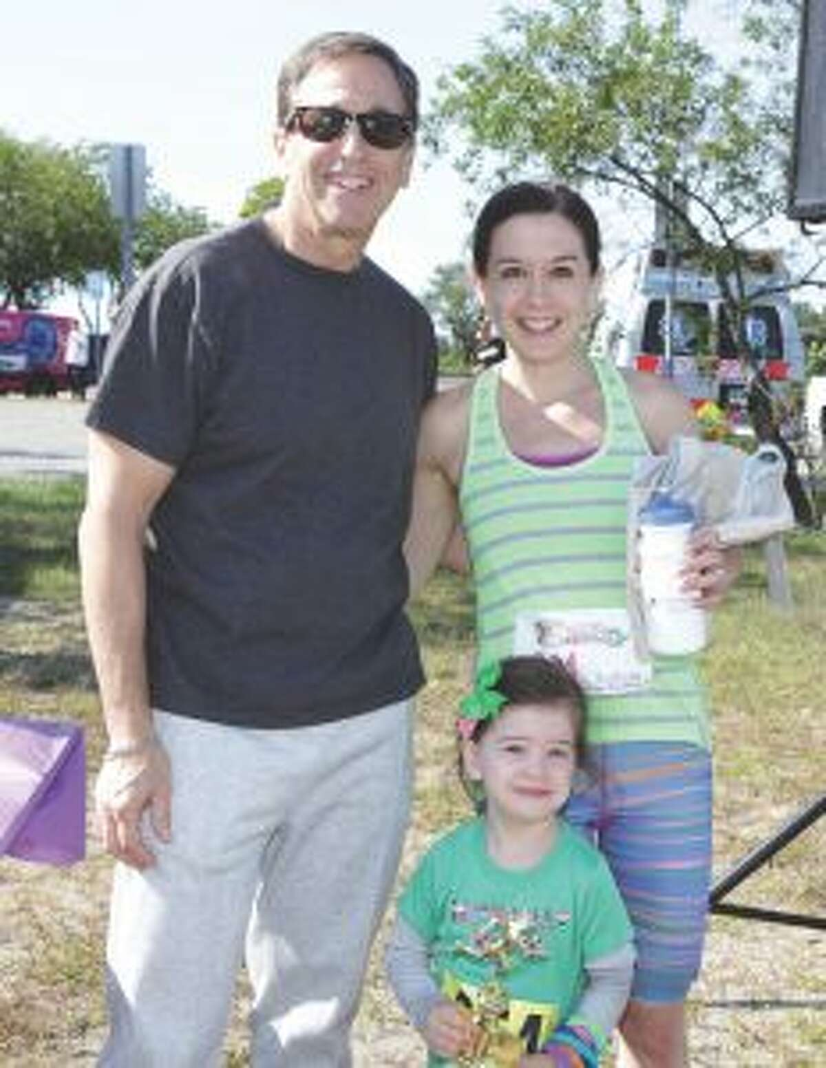 The overall winner of the 5K timed race for the Autism SpectRUN at Jennings Beach in Fairfield was Rebecca Blanchard of Stamford, pictured with her daughter Keira. She is being congratulated by Martin D. Schwartz, President and CEO of The Kennedy Center in Trumbull.