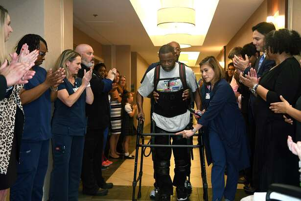 Darron Lewis, center, a stroke victim and now an outpatient at Kindred Spring Hospital, with help from Lead Physical Therapist Winnie Caras, right, demonstrates his recovery progress with the exoskeleton during an exoskeleton demonstration ribbon cutting at Kindred Spring Hospital on May 22, 2019.