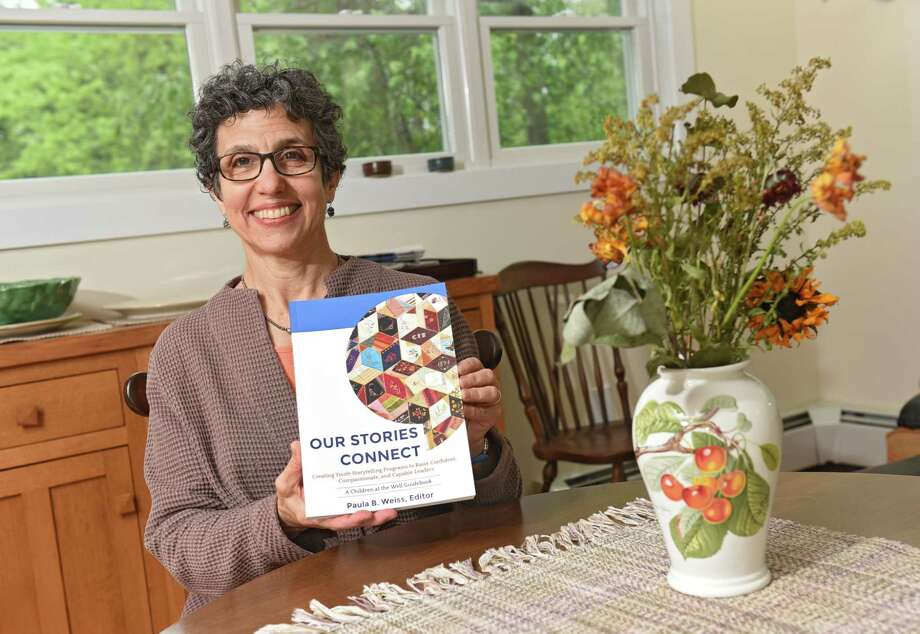 "Paula Weiss holds the book she edited all on the art and methods of in-person storytelling, titled ""Our Stories Connect"" at her home on Friday, May 17, 2019 in Cohoes, N.Y. (Lori Van Buren/Times Union) Photo: Lori Van Buren / 40046952A"