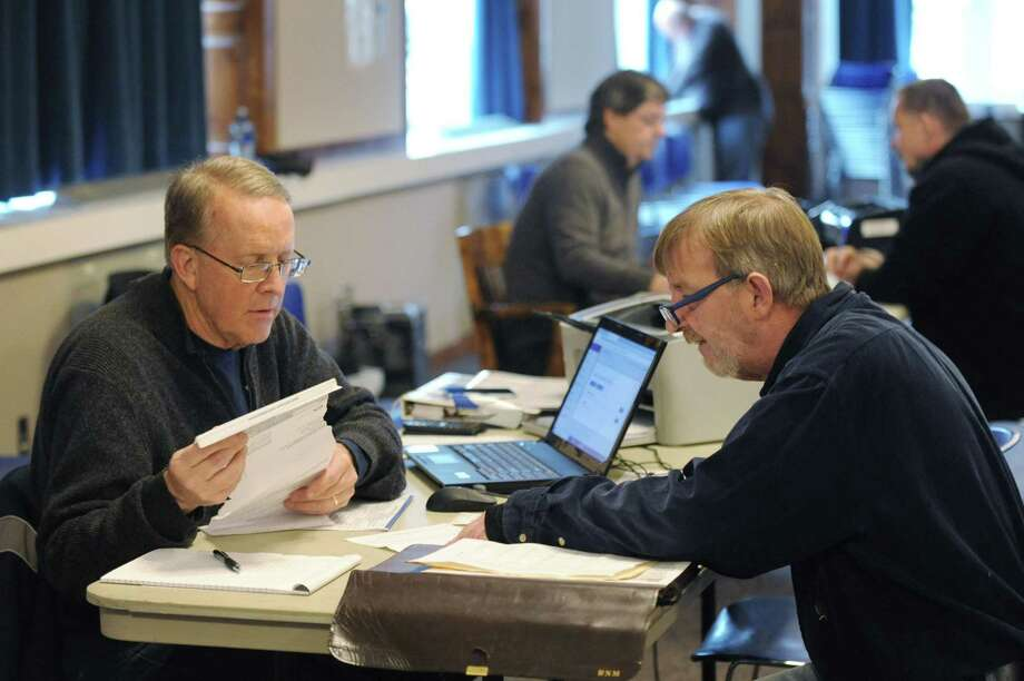 A volunteer helps a man with his tax returns as part of the VITA program. Photo: Erik Trautmann / Hearst Connecticut Media / Norwalk Hour