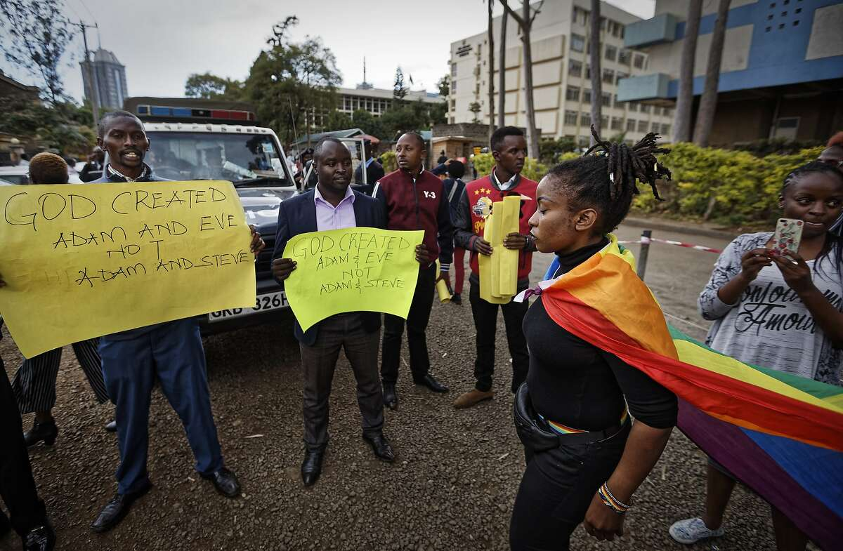 An activist supporting the LGBT community, wearing a rainbow flag, walks past a gathering of Christians opposed to the decriminalization of homosexuality, after a ruling by the High Court in Nairobi, Kenya Friday, May 24, 2019. Kenya's High Court on Friday upheld sections of the penal code that criminalize same-sex relations, a disappointment for gay rights activists across Africa where dozens of countries have similar laws. (AP Photo/Ben Curtis)