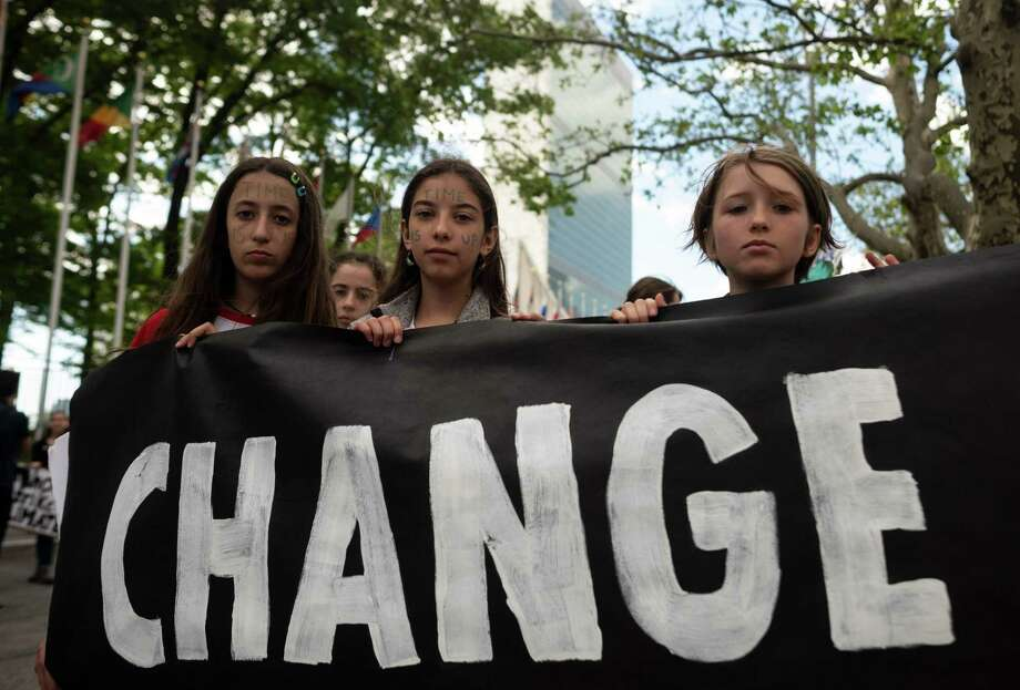 "School children hold a placard reading ""CHANGE"" during the Youth Climate Strike May 24, 2019 outside United Nations headquarters in New York City. Photo: Johannes Eisele / Getty Images / AFP or licensors"
