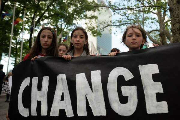 """School children hold a placard reading """"CHANGE"""" during the Youth Climate Strike May 24, 2019 outside United Nations headquarters in New York City."""