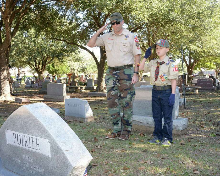 Jack Armenta, 10, of Boy Scout Pack 548 and his father Ben Armenta salute after laying a wreath at the grave of a military veteran on National Wreaths Across America Day at Magnolia Cemetery, Saturday, Dec. 15, 2018 in Katy. On Monday, Memorial Day ceremonies will be held at the cemetery beginning at 10 a.m. under the direction of Katy Veterans of Foreign Wars Post 9182. Photo: Craig Moseley, Houston Chronicle / Staff Photographer / ©2018 Houston Chronicle
