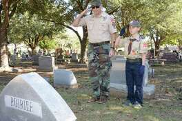 Jack Armenta, 10, of Boy Scout Pack 548 and his father Ben Armenta salute after laying a wreath at the grave of a military veteran on National Wreaths Across America Day at Magnolia Cemetery, Saturday, Dec. 15, 2018 in Katy. On Monday, Memorial Day ceremonies will be held at the cemetery beginning at 10 a.m. under the direction of Katy Veterans of Foreign Wars Post 9182.