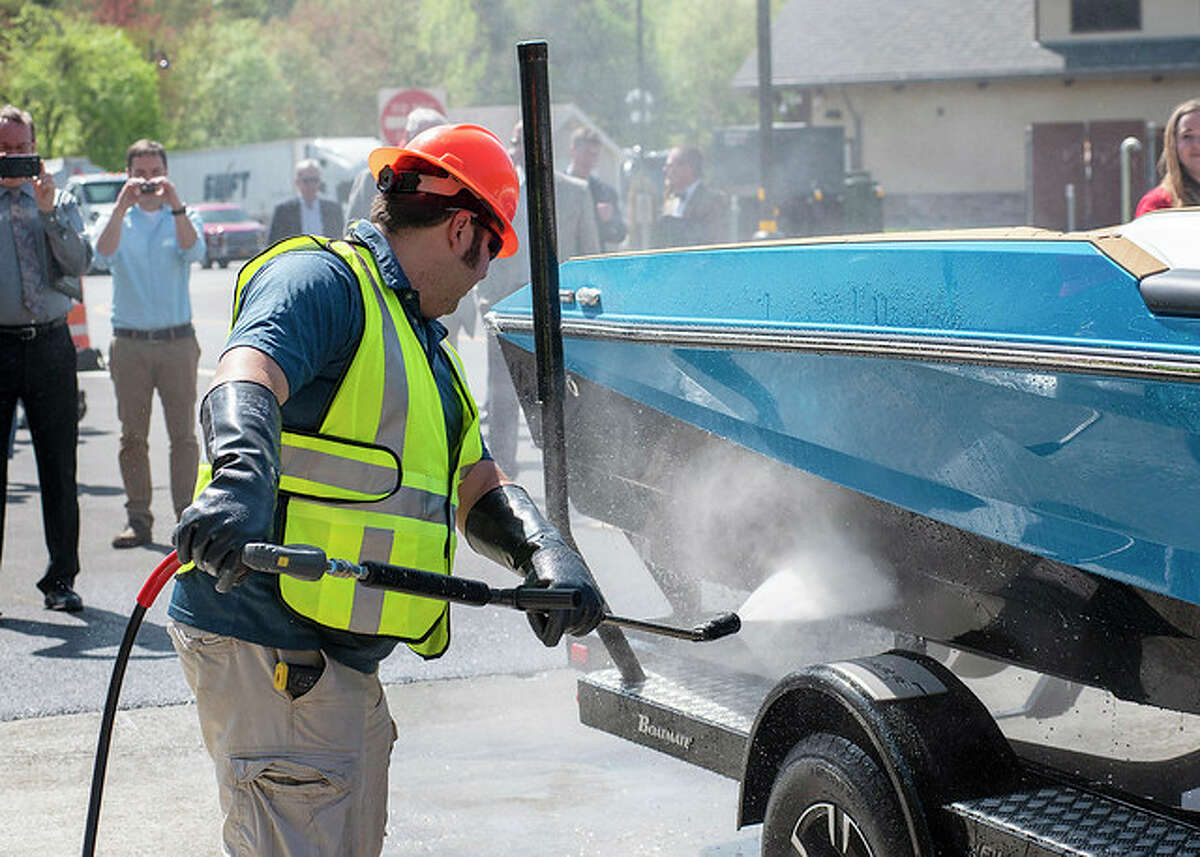 A worker uses a high-pressure hose to clean the outside of a boat of potential invasive species.