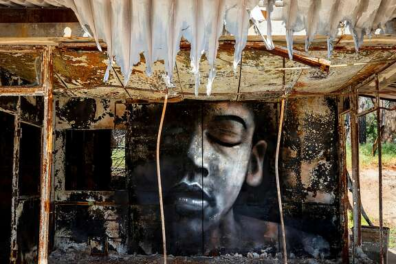 A mural painted by artist Shane Grammer is seen on the wreckage of a storage facility damaged by last year's Camp Fire along Skyway in Paradise, Calif. Saturday, May 4, 2019.