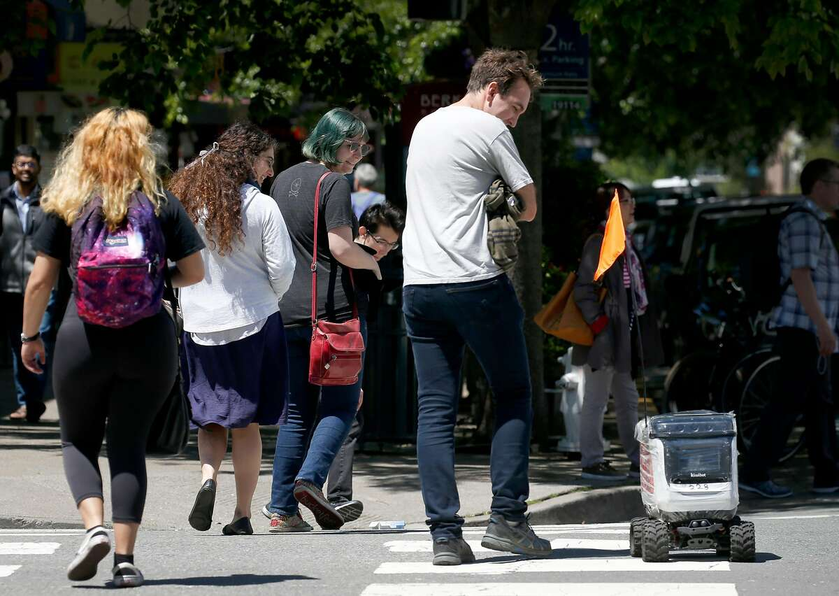 A Kiwi food delivery robot causes heads to turn while crossing the intersection of Oxford and Center streets in Berkeley, Calif. on Wednesday, May 22, 2019. As many as 20 of the rolling containers are deployed in the UC Berkeley campus area delivering meals remotely to customers from several area restaurants.