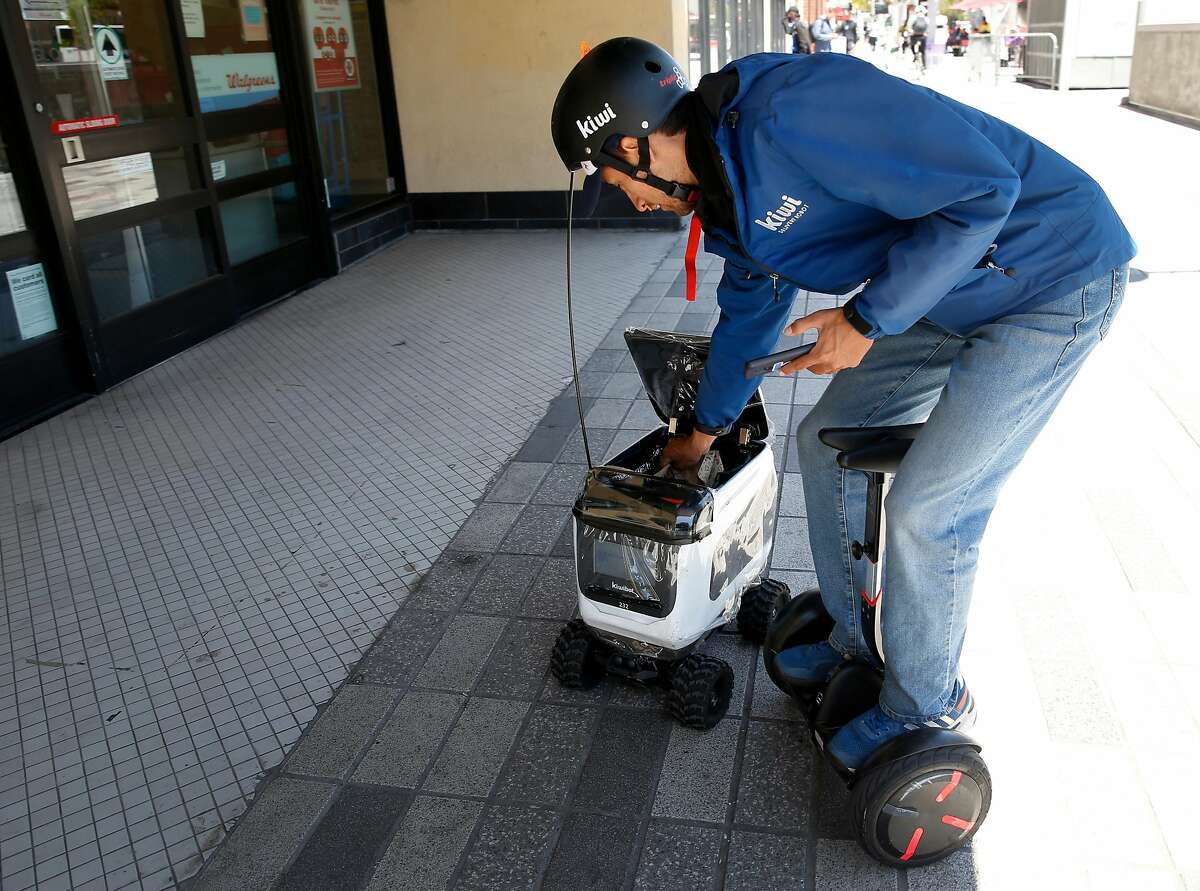 Kiwi employee Andres Rosero places a lunch order from Chipotle on Shattuck Avenue into one of the company's food delivery service robots that will deliver it to a customer in Berkeley, Calif. on Wednesday, May 22, 2019. As many as 20 of the rolling containers are deployed in the UC Berkeley campus area delivering meals remotely to customers from several area restaurants.