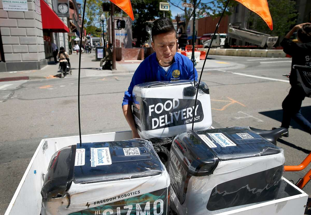 Carlos Cumelo loads Kiwi robots onto a bicycle cart on Shattuck Avenue to transport them to a staging area one block away on Oxford Street for a day of food delivery service in Berkeley, Calif. on Wednesday, May 22, 2019. As many as 20 of the rolling containers are deployed in the UC Berkeley campus area delivering meals remotely to customers from several area restaurants.