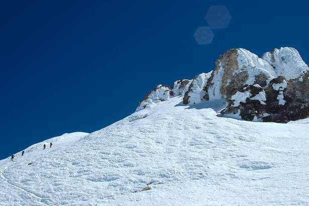 A group of trekkers descend from Mount Shasta's 14,179-foot summit, a lava plug dome crowned by a volcanic pinnacle