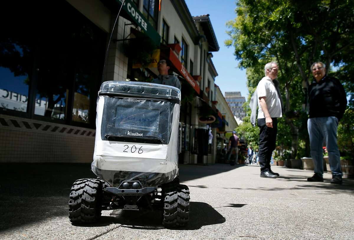 A Kiwi food delivery robot rolls up Center Street towards a staging area on Oxford Street in Berkeley, Calif. on Wednesday, May 22, 2019. As many as 20 of the rolling containers are deployed in the UC Berkeley campus area delivering meals remotely to customers from several area restaurants.