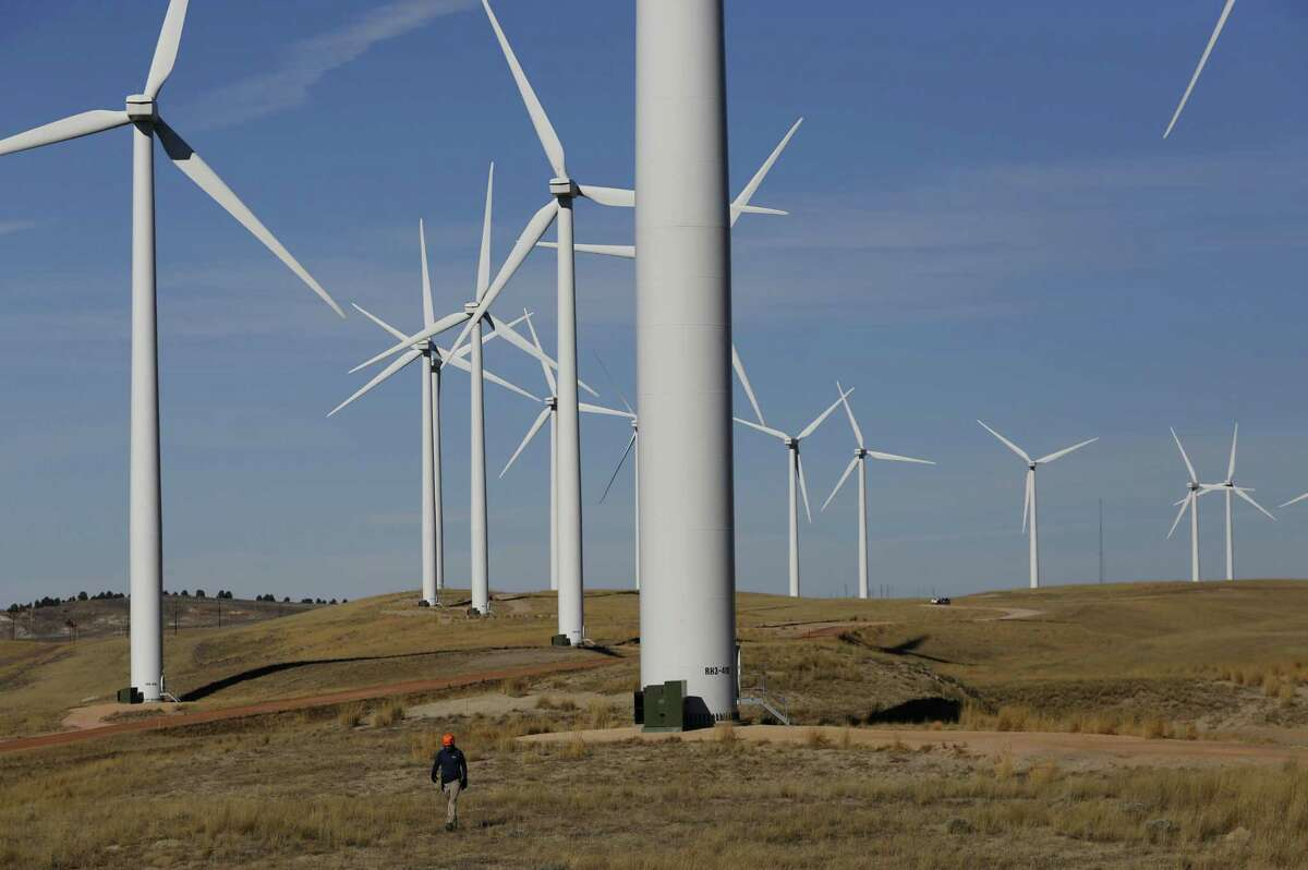 A biologist from West Inc., which provides environmental contracting services for PacifiCorp, walks a grid Thursday, Nov. 15, 2018 while looking for carcasses of birds that may have hit a turbine at the company's multi-project wind development near Rolling Hills in Converse County, Wyoming. PacifiCorp collects and documents all birds and bats that may have been killed by a turbine. (Alan Rogers/The Casper Star-Tribune via AP)