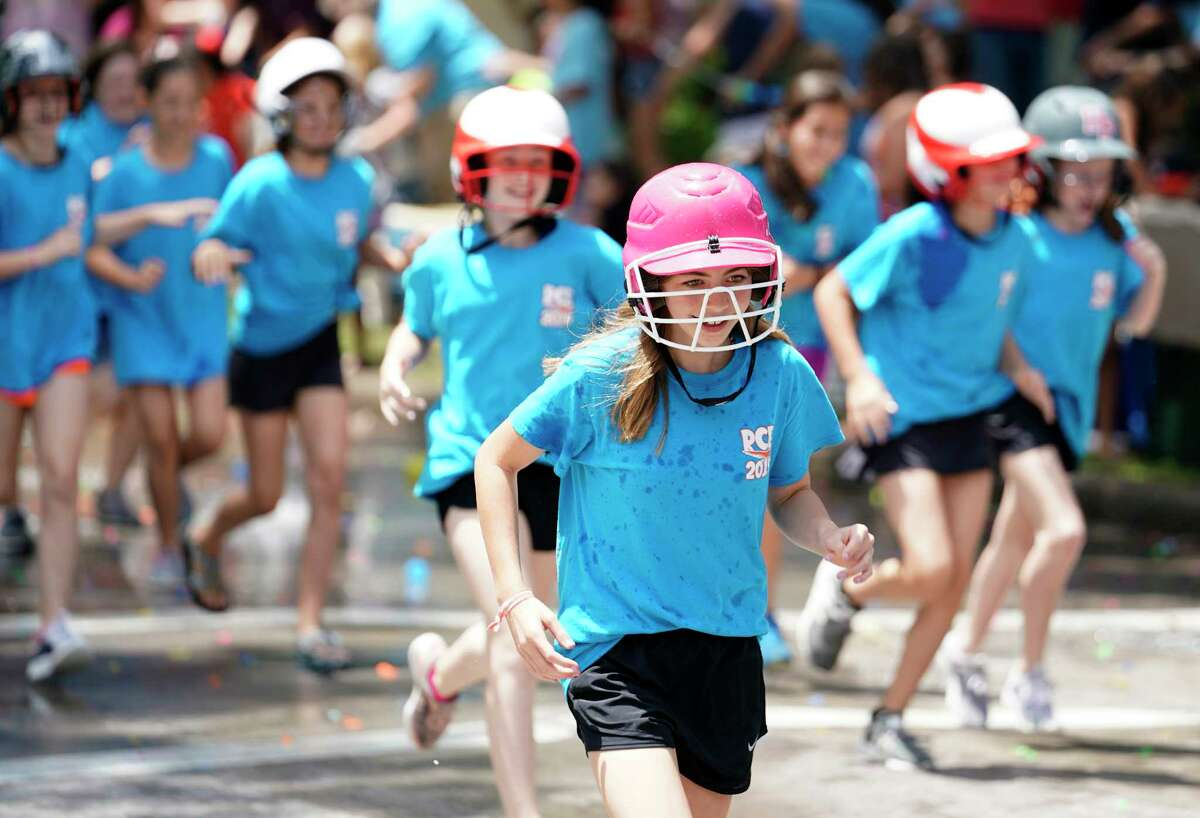 Fifth graders of Rummel Creek Elementary are greeted with water balloons as they run along Brittmoore on the last day of school during the annual