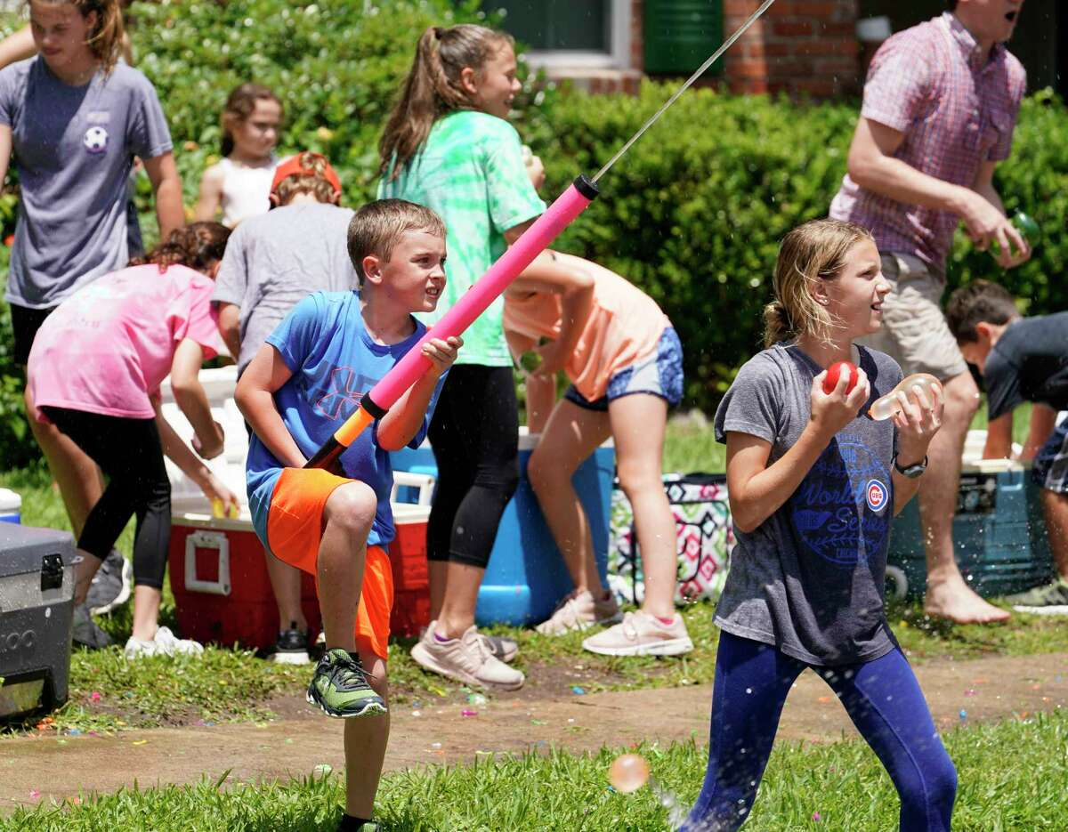 Kids continue to play after throwing water balloons at the fifth graders of Rummel Creek Elementary who ran along Brittmoore on the last day of school during the annual