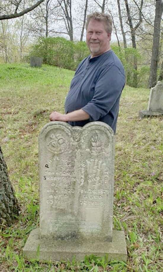 Fred Sharpsteen stands with the grave of his ancestors who are buried in the old Bay Port Cemetery. He and about 50 others met to clean up the site for Memorial Day. (Submitted Photo)