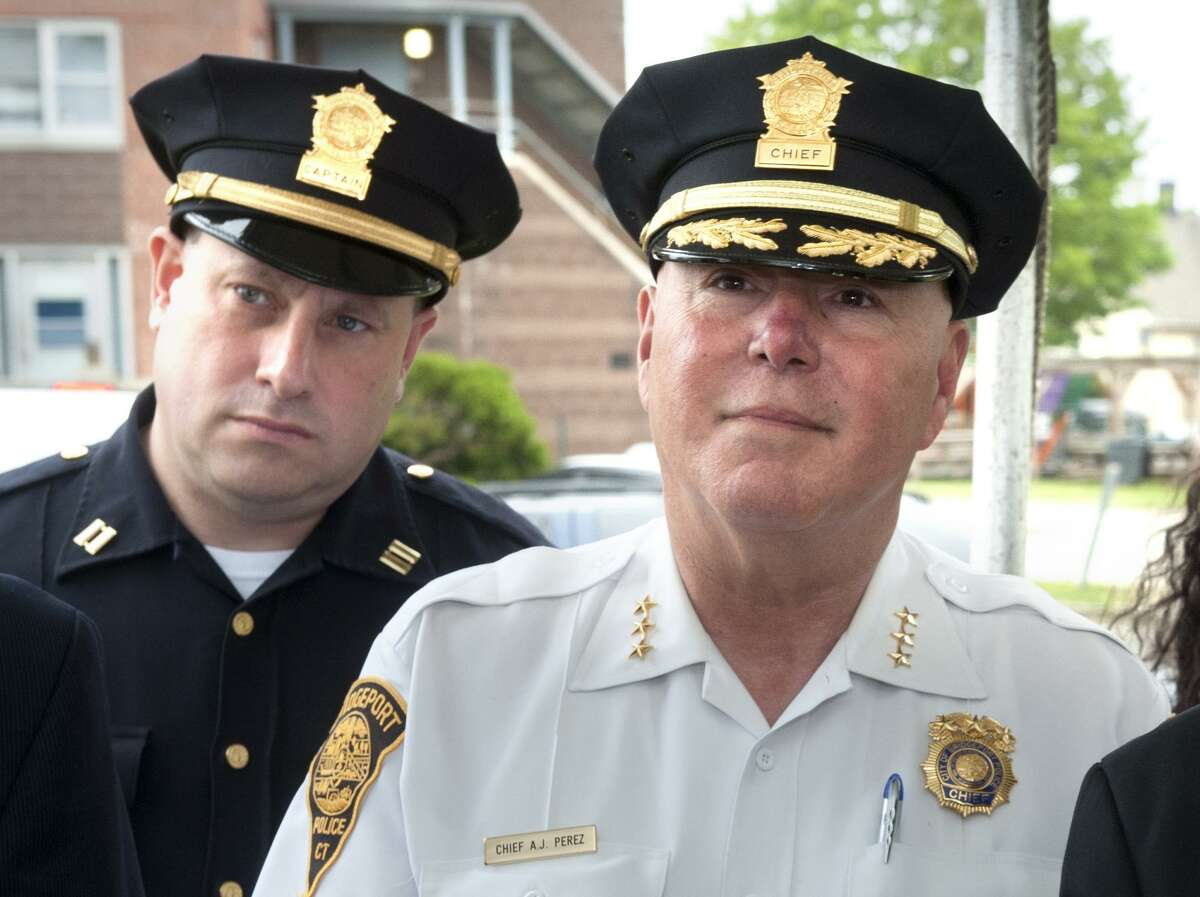 """Police Captain Mark Straubel, left, stands behind Chief Armondo """"A.J."""" Perez during a press conference at the Charles F. Greene Homes in Bridgeport, Conn. June 16, 2017."""