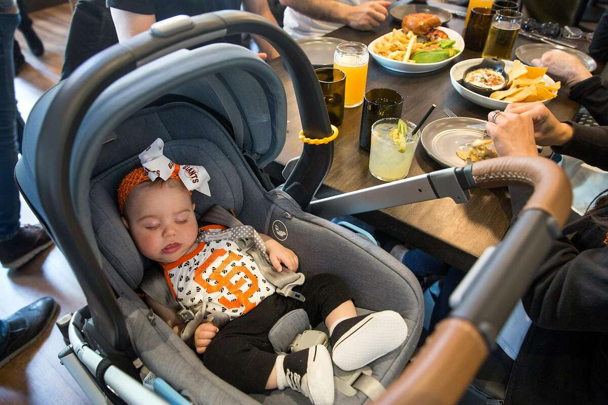 Charlotte, 4 months, takes a nap while her mother, Jayne Carini, enjoys a meal with family and friends at The Brixton restaurant. They are headed to the San Francisco Giants game on Thursday, May 23, 2019. San Francisco, Calif.