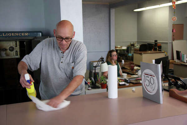 Custodian Paul Jungk cleans the front counter for the final time Friday at The Edwardsville Intelligencer's North Second Street office. The newspaper office will begin to relocate to a new space on North Main Street next week. In the background is circulation manager Melissa Pitts.