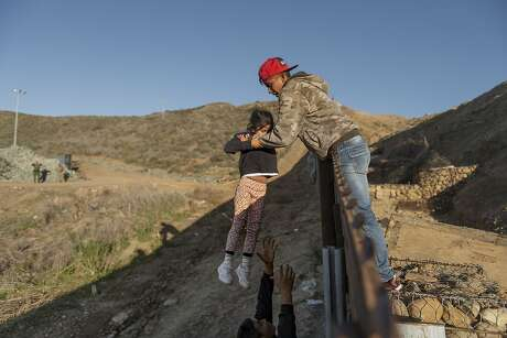 FILE - In this Jan. 3, 2019, file photo, a migrant from Honduras passes a child to her father after he jumped the border wall to get into the U.S. side to San Diego, Calif., from Tijuana, Mexico. A federal judge is expected to decide Friday, May 24 whether to block the White House from spending billions of dollars to build a wall on the Mexican border with money secured under President Donald Trump's declaration of a national emergency. (AP Photo/Daniel Ochoa de Olza, File)