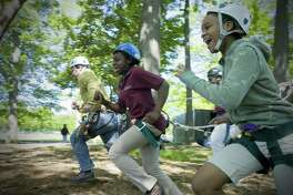 Seventh-grade students Kayla Banner, 12, and Elexis Boyd, 12, from Trailblazers Academy participate in a ropes course trust-building activity as part of the Girls Empowerment Movement youth program.
