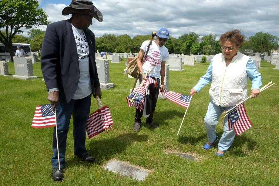 Bridgeport City Council member Maria Valle works with Saunders Jordan and Lawrence Lesley, both U.S. Army veterans as they place American flags on the graves of veterans buried in St. Michael's Cemetery, in Stratford, Conn. May 24, 2019. They were part of a large group of volunteers who helped clean up the graves and place flags in advance of Memorial Day. Photo: Ned Gerard / Hearst Connecticut Media / Connecticut Post