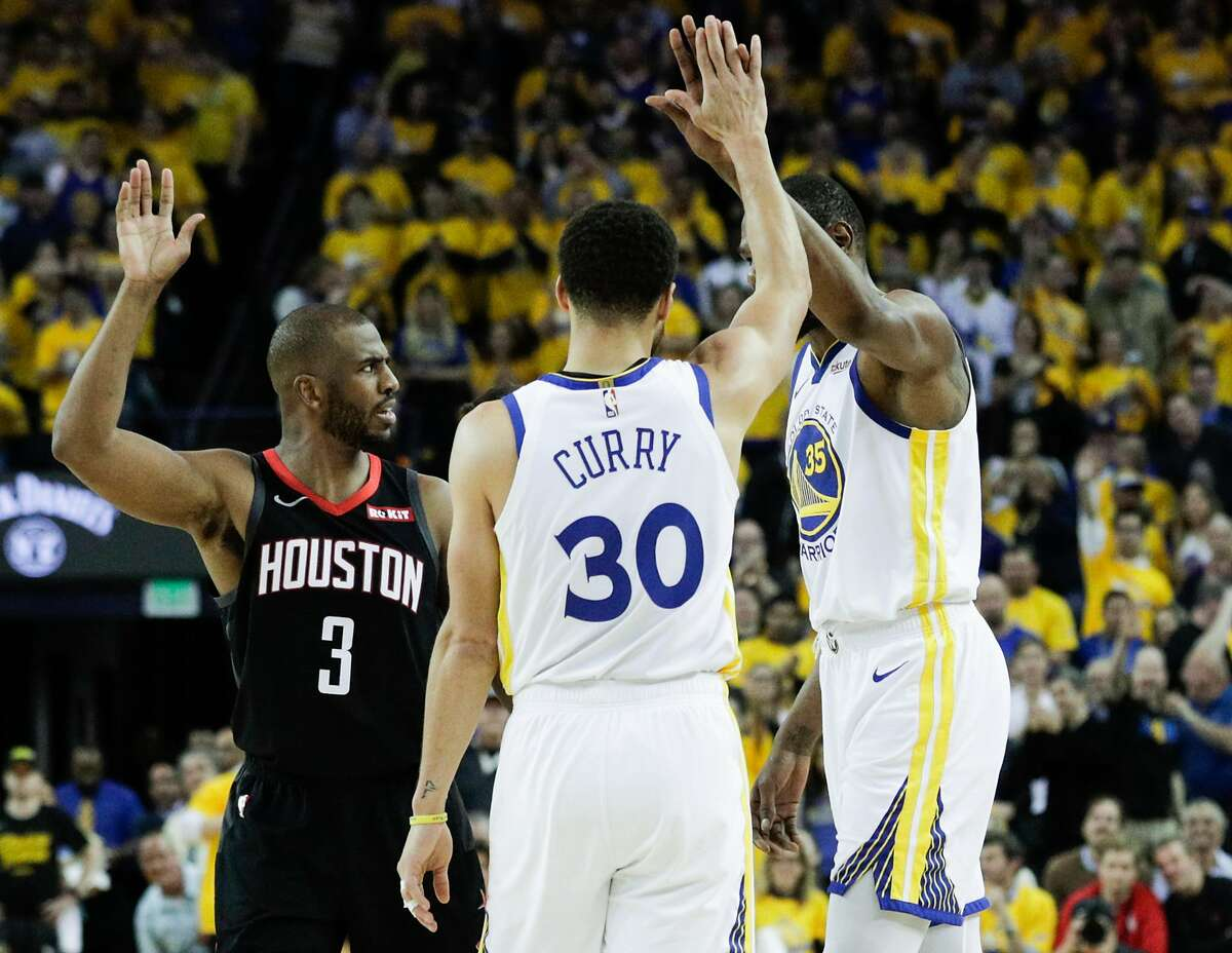 Golden State Warriors Stephen Curry and Kevin Durant high five as Houston Rockets Chris Paul is called for a foul in the second quarter during game 5 of the Western Conference Semifinals between the Golden State Warriors and the Houston Rockets at Oracle Arena on Wednesday, May 8, 2019 in Oakland, Calif.