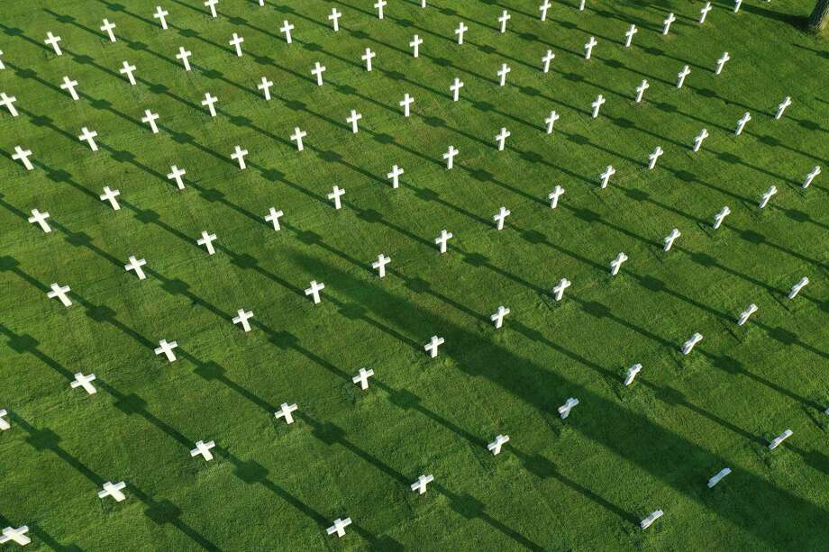 In this aerial view crosses stand over graves at Normandy American Cemetery on April 30, 2019 at Colleville-sur-Mer, France. The cemetery contains the remains of 9,380 U.S. soldiers killed during the Allied Normandy invasion. June 6, 2019, will mark the 75th anniversary of the D-Day invasion, in which a massive Allied force of U.S., British, Canadian, French and troops from other nationalities landed at beaches in Normandy to begin their push to liberate France from Nazi occupation during World War II. (Photo by Sean Gallup/Getty Images) Photo: Sean Gallup / Getty Images / 2019 Getty Images