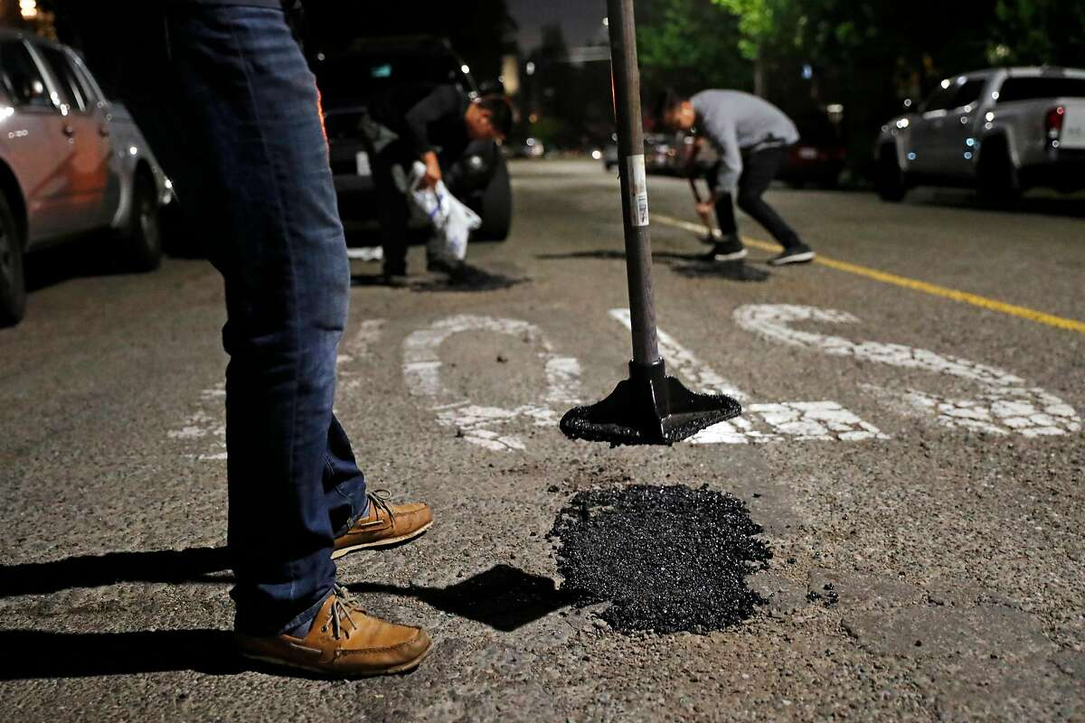 Pothole Vigilantes' Brian, Eric and PV fill potholes on Perkins Street in Oakland, Calif., on Wednesday, May 22, 2019.