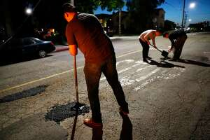 Pothole Vigilantes' Brian, PV and Eric fill potholes on Perkins Street in Oakland, Calif., on Wednesday, May 22, 2019.