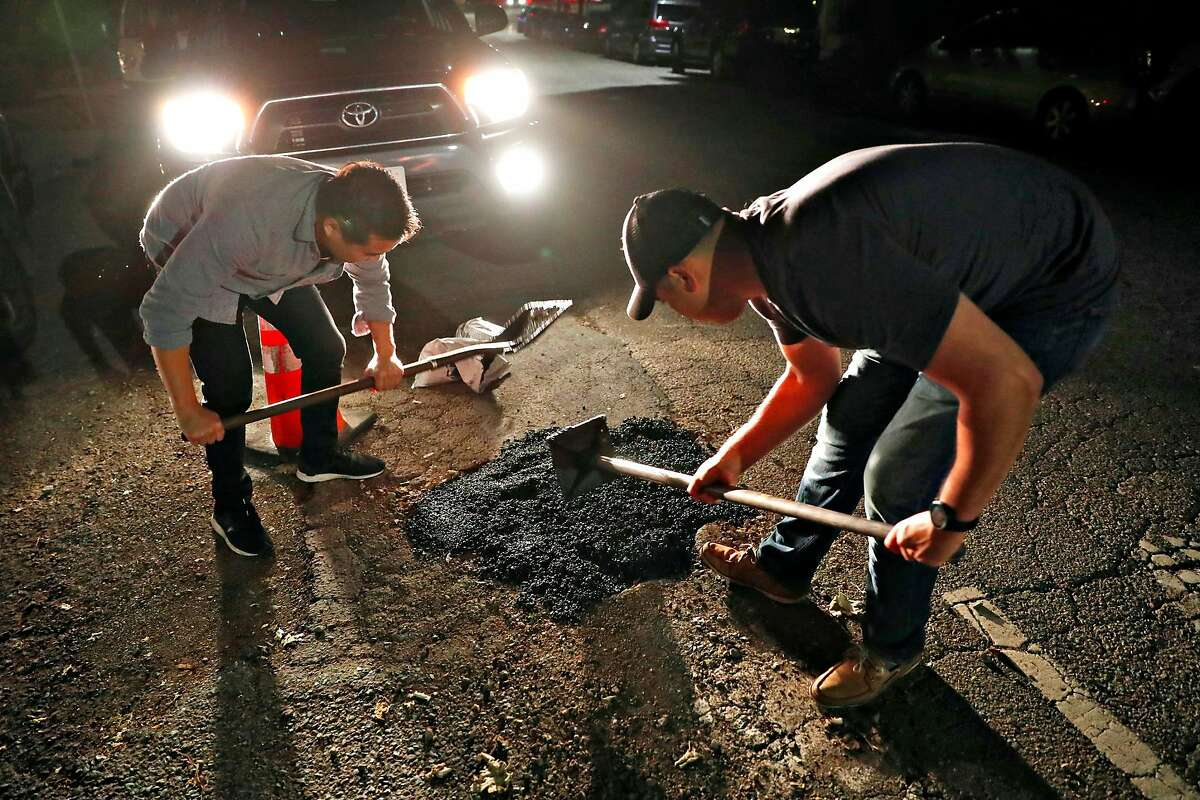 Pothole Vigilantes' PV and Brian fill a pothole on Perkins Street in Oakland, Calif., on Wednesday, May 22, 2019.