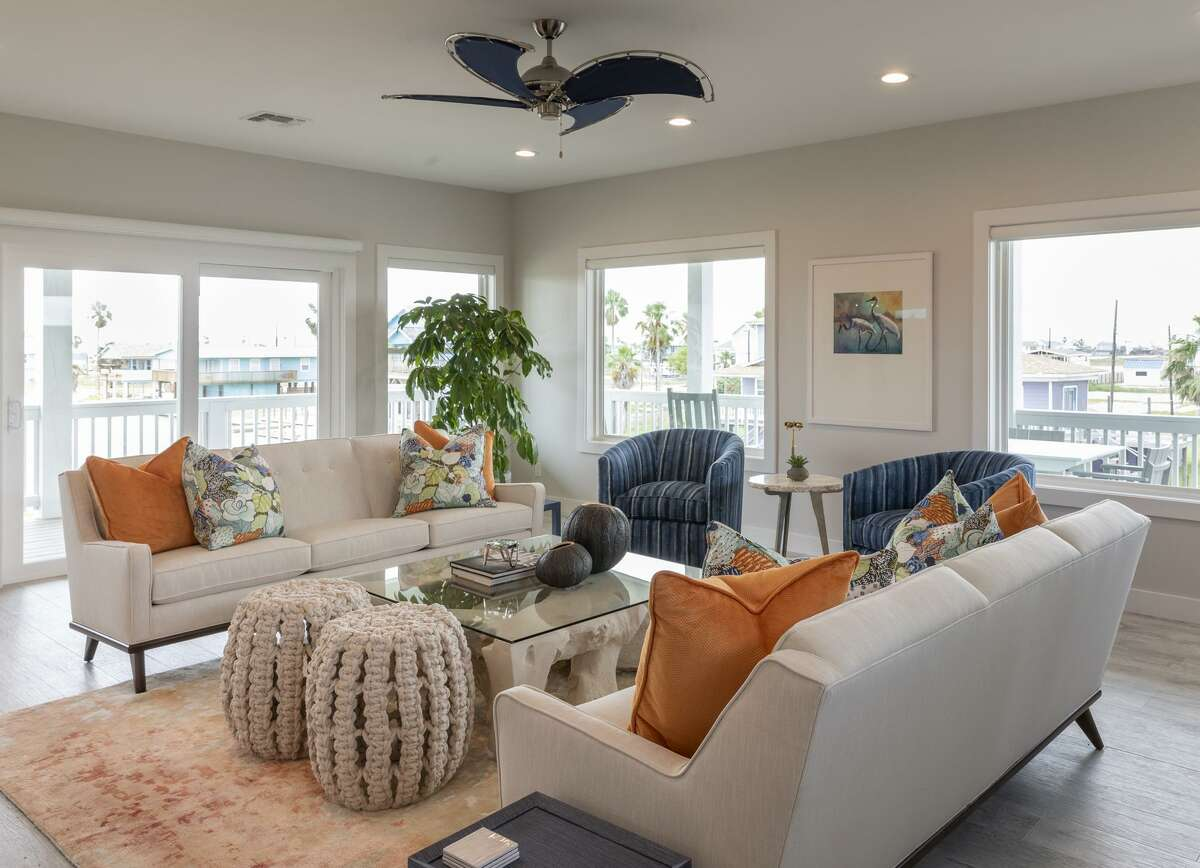 The living room in Sandy and Dr. J.J. Diaz's Rockport home has white sofas with blue and orange accents, all with a coastal feel. The home looks out at Copano Bay.