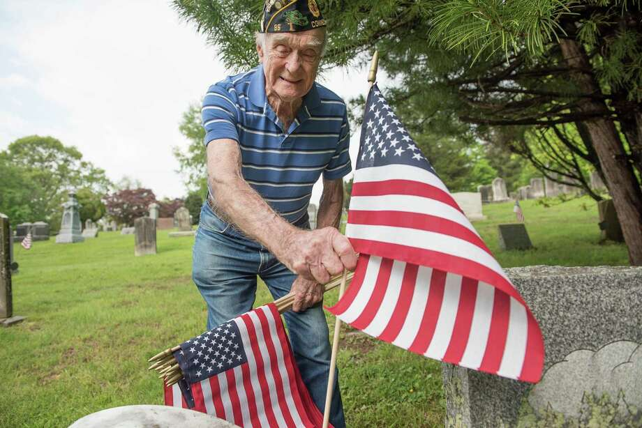 Air Force veteran Bing Ventres places a flag at the grave of a veteran at Hillside Cemetery in Wilton, Conn., May 20. A reader asks everyone to gather this Memorial Day in remembrance of those who sacrificed their lives for their nation. Photo: Bryan Haeffele / / Bryanhaeffele.com /Hearst Connecticut Media / BryanHaeffele