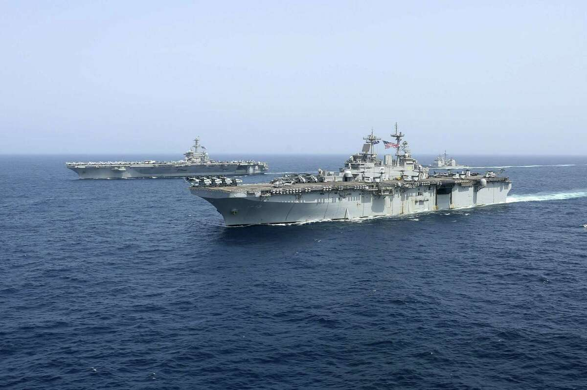 USS Kearsarge sails in front of the USS Abraham Lincoln aircraft carrier in the Arabian Sea. The United States sent an aircraft carrier, bombers and missile defense systems to the Persian Gulf region in May 2019.