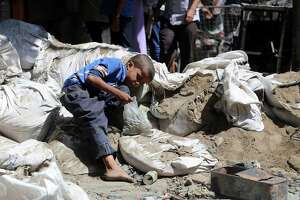A Yemeni boy looks for bullet casings, to sell as scrap metal, in a street in an old market on April 27, 2019, in Yemen's third city of Taiz after clashes between pro-government militias left two children dead. The U.S. must withhold military supplies from Saudi Arabia to end this conflict, which has become a humanitarian crisis.