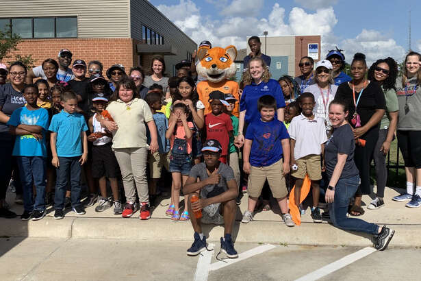 CeCe Kizer and Dash/Dynamo mascot Diesel visited kids at a field day put on by Buckner International on Friday.
