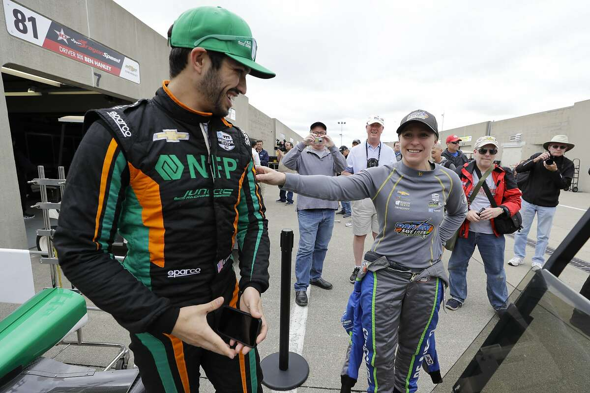Kyle Kaiser, left, and Pippa Mann, of England, talk in the garage area before the start of practice for the Indianapolis 500 IndyCar auto race at Indianapolis Motor Speedway, Monday, May 20, 2019, in Indianapolis. (AP Photo/Darron Cummings)