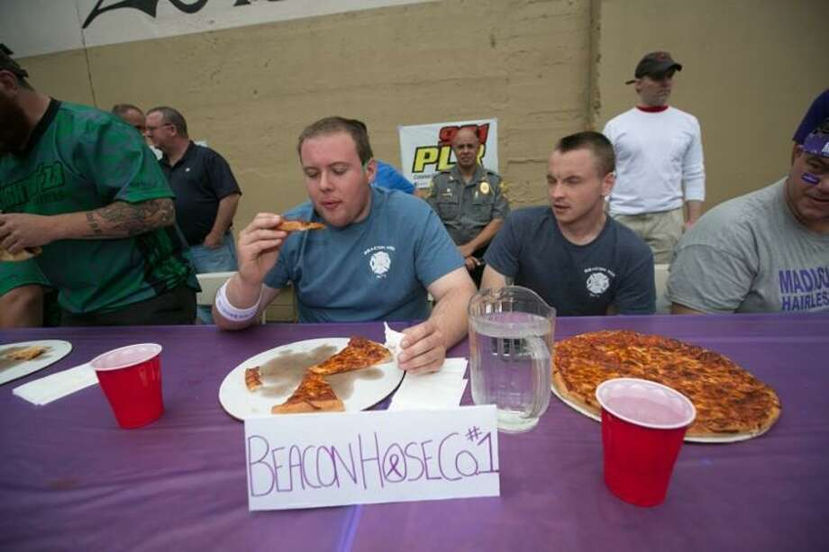 """Participants chow down on pizza at a prior""""My Big Fat Greek Style Pizza Eating Contest."""" Photo: Project Purple / Contributed Photo"""