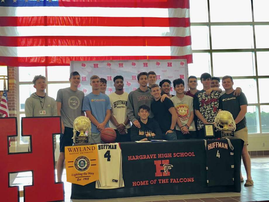 Surrounded by his Hargrave High School teammates, senior Gage Hulse signs a scholarship offer to play college basketball at Wayland Baptist University during a signing ceremony at the school on the morning of May 24 Photo: Elliott Lapin / Staff Photo