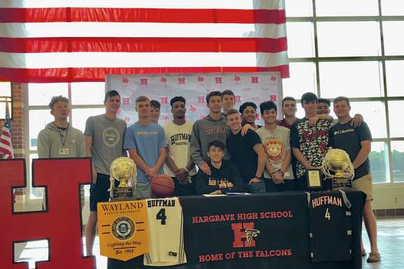 Surrounded by his Hargrave High School teammates, senior Gage Hulse signs a scholarship offer to play college basketball at Wayland Baptist University during a signing ceremony at the school on the morning of May 24