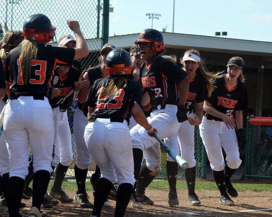 Edwardsville's Maria Smith, jumping, celebrates a first-inning leadoff home run with her teammates on Friday during the championship game of the Edwardsville Class 4A Regional. Photo: Scott Marion/The Intelligencer