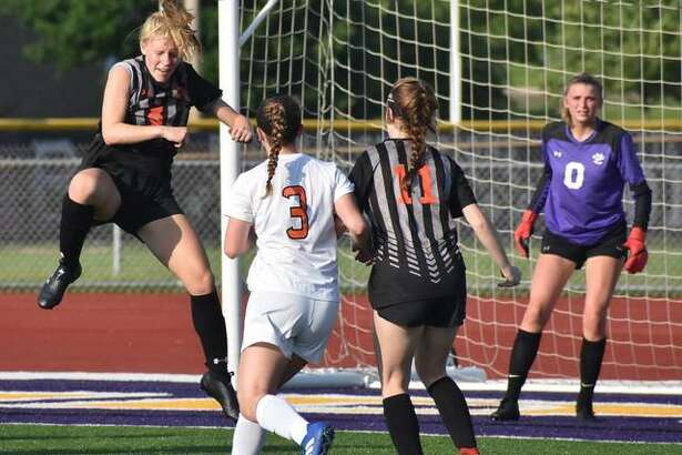 Edwardsville's Sarah Kraus, left, goes up for a head ball near the 18-yard box on Friday in Bloomington.