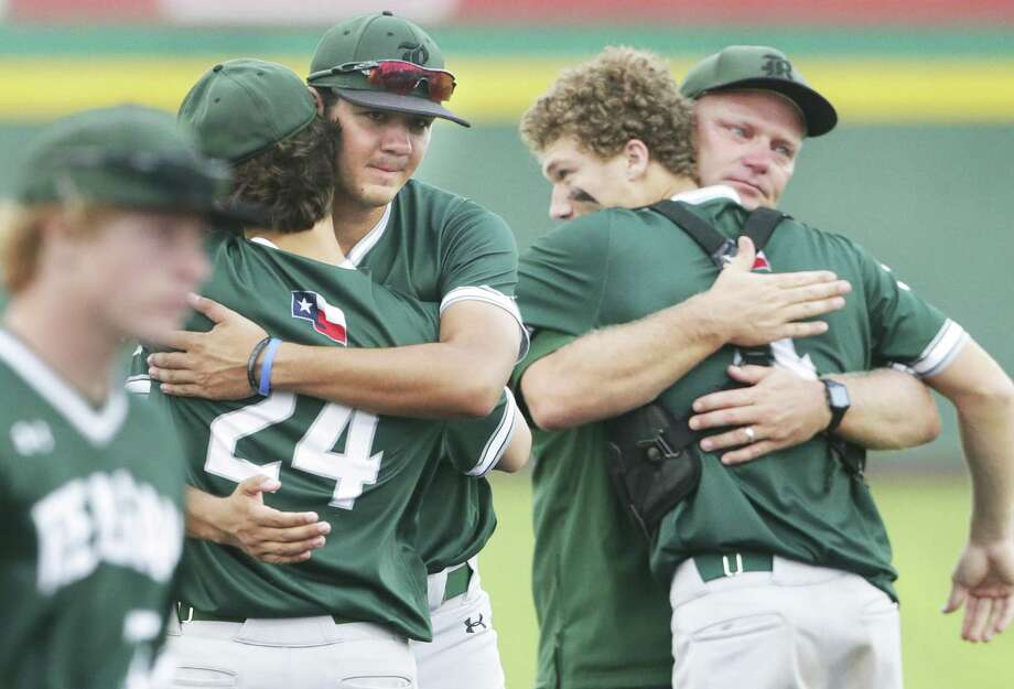 Rattler seniors Cal Martin, center, and Alec Caven, right center, get hugs from teammates and coach Chans Chapman as Reagan loses to Alexander 8-9 in game 2 of the Class 6A Regional Semifinals at Cabaniss Field in Corpus Christi on May 24, 2019. Photo: Tom Reel, Staff / Staff Photographer / 2019 SAN ANTONIO EXPRESS-NEWS